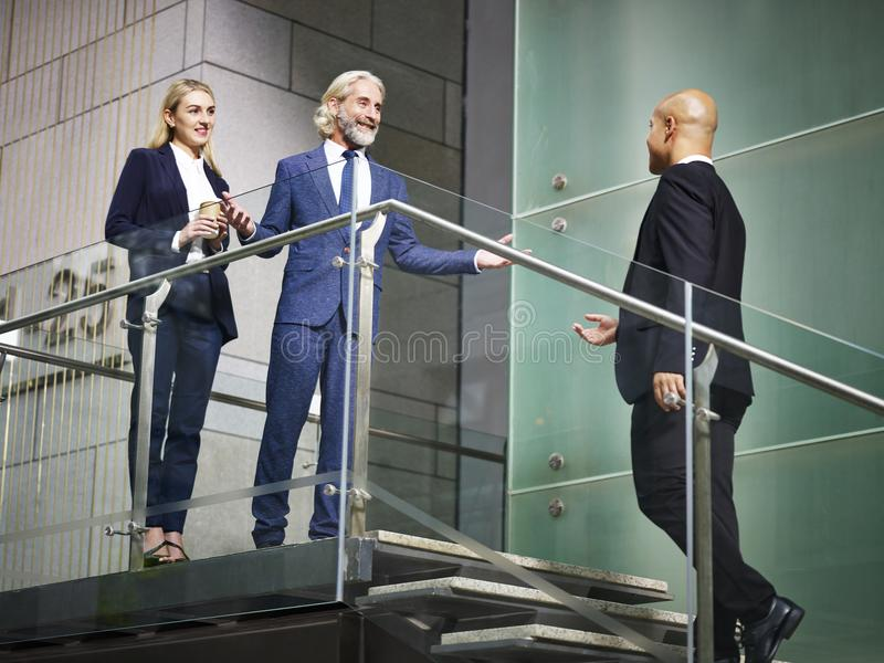 Senior corporate executive welcoming visitor on stair of modern. Office building, low angle view royalty free stock images