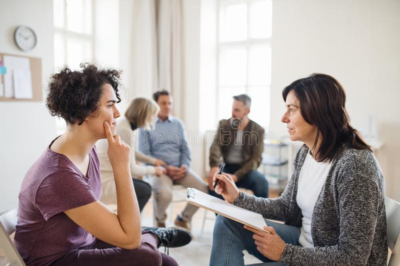 Senior counselor with clipboard talking to a woman during group therapy. royalty free stock photos