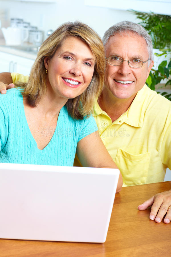 Senior couple. Seniors couple working with laptop at home stock images