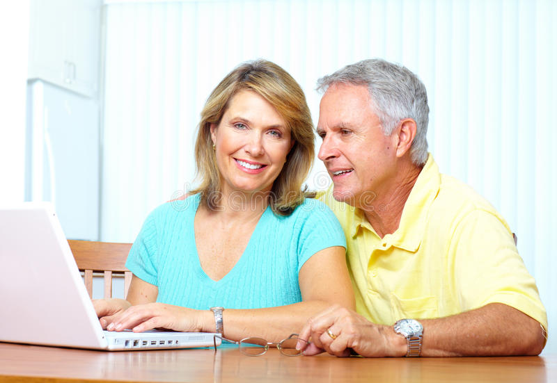 Senior couple. Seniors couple working with laptop at home royalty free stock photo