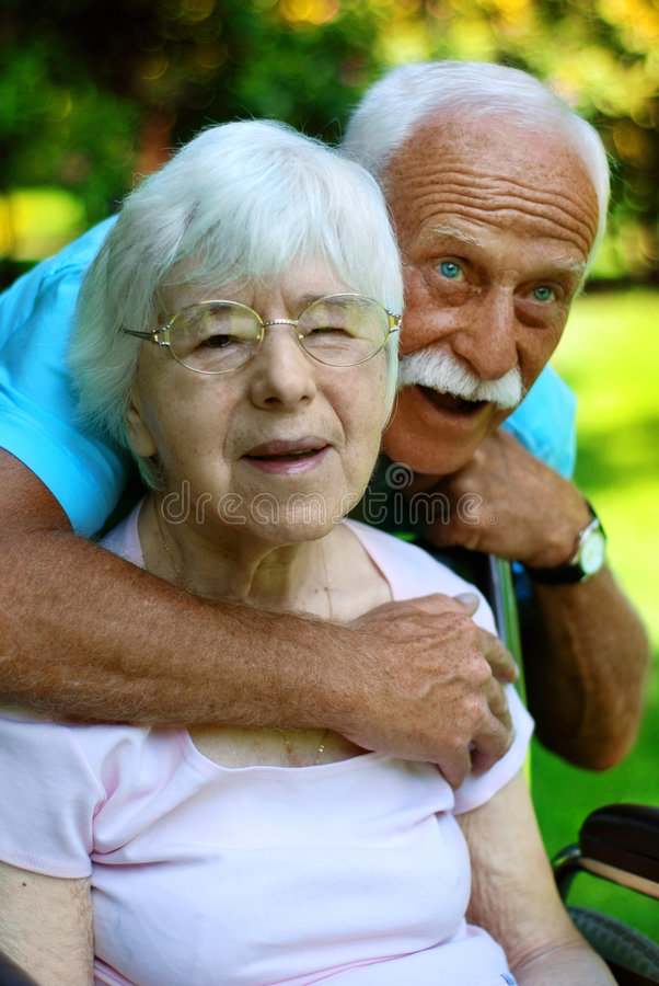 Senior couple. In the park . They are smiling and talking