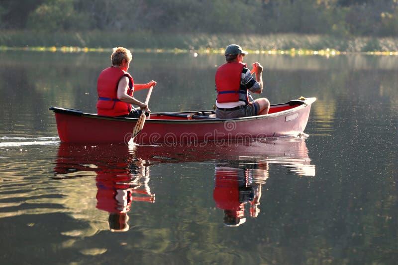 Senior couple. Paddling canoe on a lake royalty free stock image