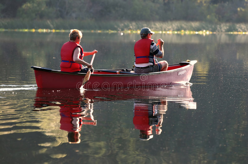 Senior couple. Paddling canoe on a lake