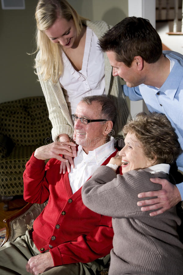 Senior couple with adult children. Together at home stock photo