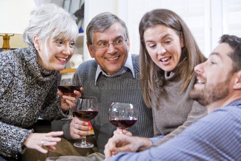 Senior couple, adult children talking and drinking stock photo