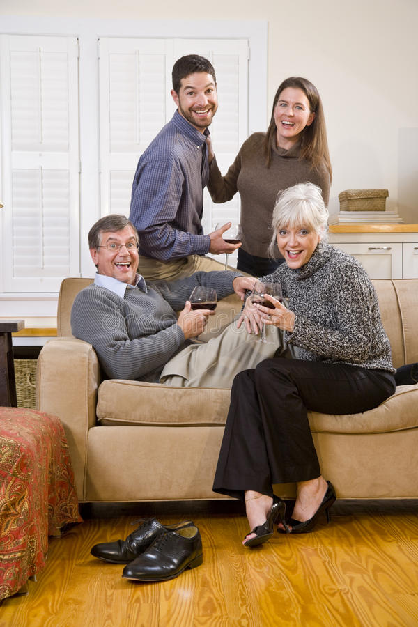 Senior couple, adult children talking and drinking stock image
