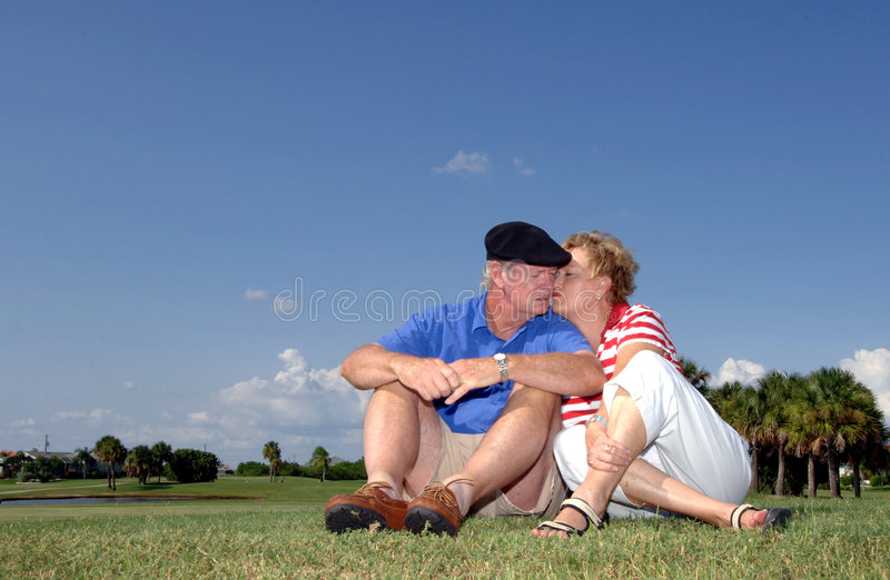 Senior couple affection. A senior couple kissing outdoors