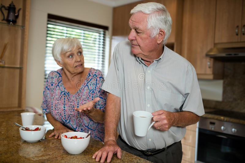 Senior couple arguing in kitchen. At home stock image