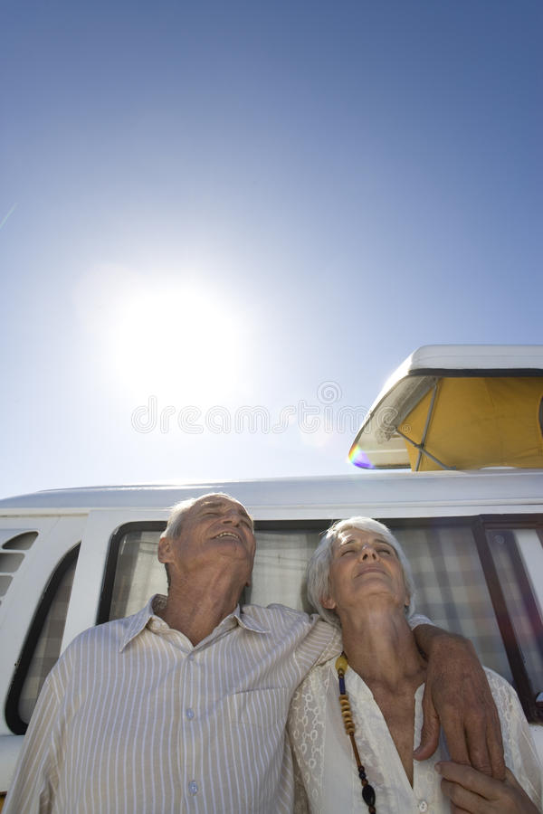 Senior couple arm in arm against camper van, low angle view royalty free stock photography