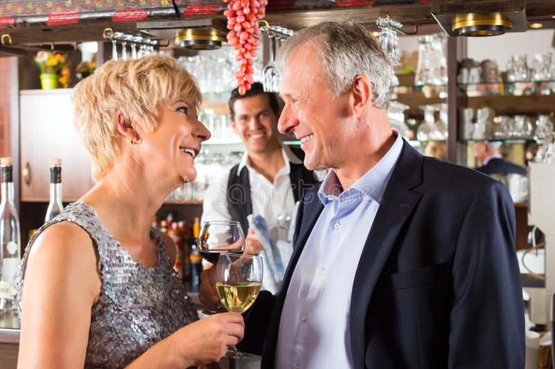 Download Senior Couple At Bar With Glass Of Wine In Hand Stock Photo - Image of clink, bartender: 28158330