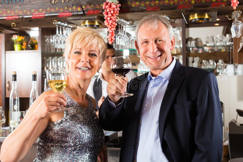 Download Senior Couple At Bar With Glass Of Wine In Hand Stock Photo - Image: 28158406