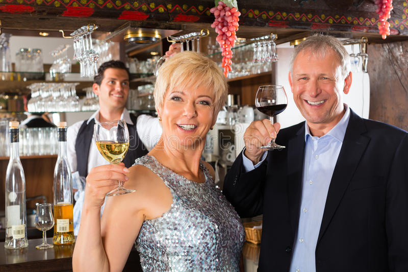Download Senior Couple At Bar With Glass Of Wine In Hand Stock Image - Image: 28158539