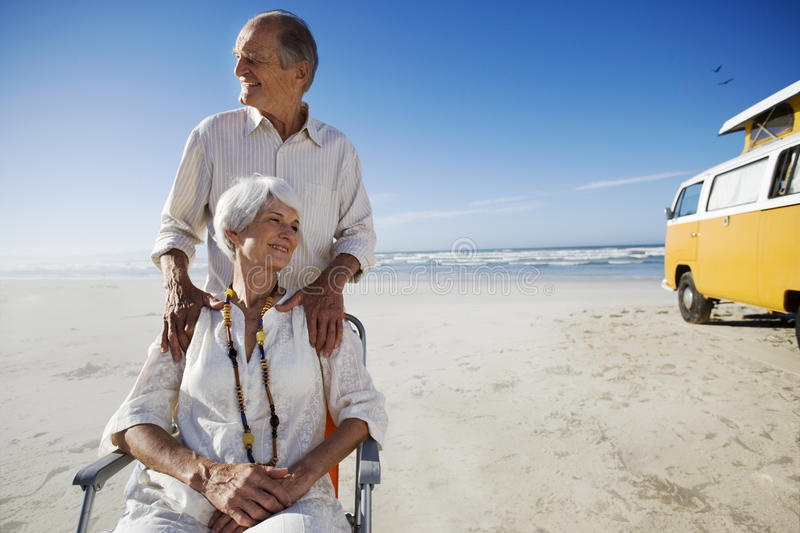 Senior couple on beach by camper van, man behind woman in chair, smiling. Senior couple on beach by camper van, men behind women in chair, smiling royalty free stock images