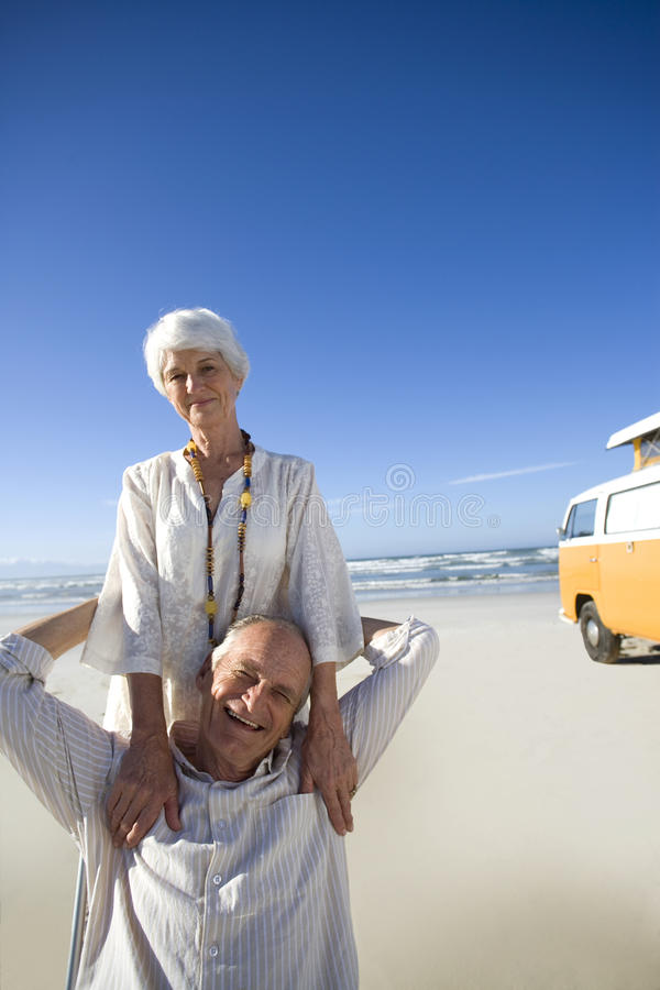 Senior couple on beach by camper van, smiling, portrait royalty free stock photography