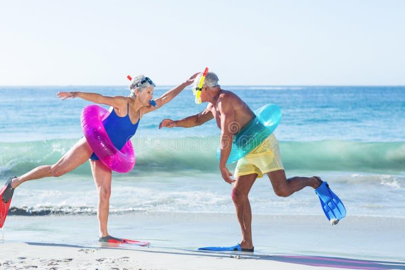 Senior couple with beach equipment stock photography