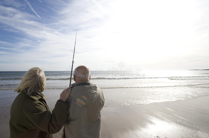 Senior couple on beach looking out to sea, man with fishing rod, rear view (lens flare). Senior couple on beach looking out to sea, men with fishing rod, rear stock image
