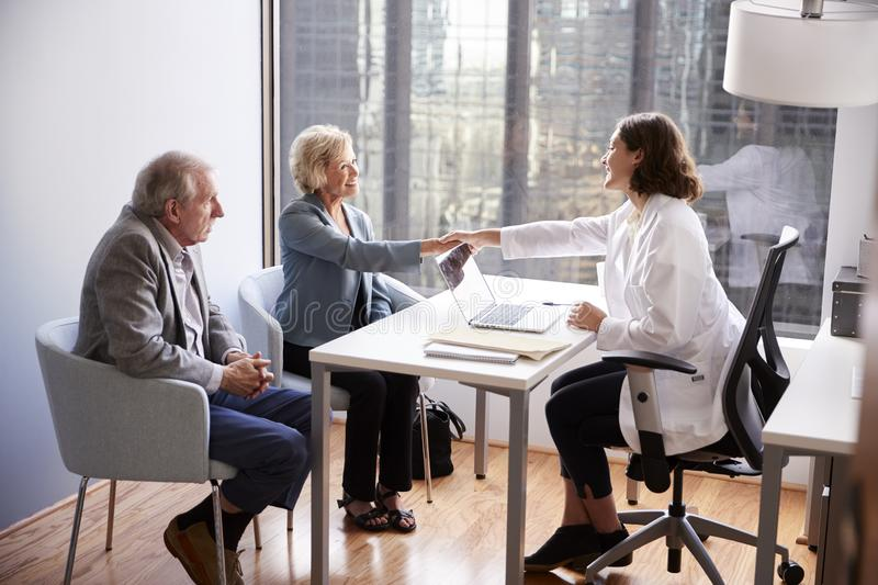 Senior Couple Being Greeted By Female Doctor With Handshake On Visit To Hospital For Consultation stock photos