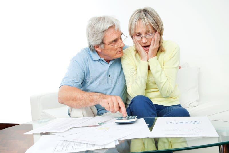 Senior couple with bills stock photography