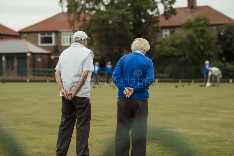 Senior Couple at Bowling Green. A rear view shot of a senior couple spectating a lawn bowling game, standing with their hands behind their back royalty free stock image