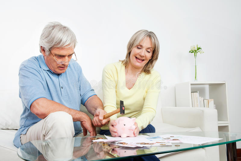 Senior couple breaking piggy bank royalty free stock photo