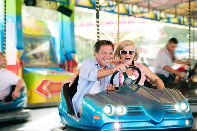 Senior couple in the bumper car at the fun fair stock photos