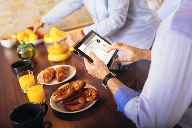 Senior couple busy look at digital tablet while having delicious breakfast at home kitchen stock images