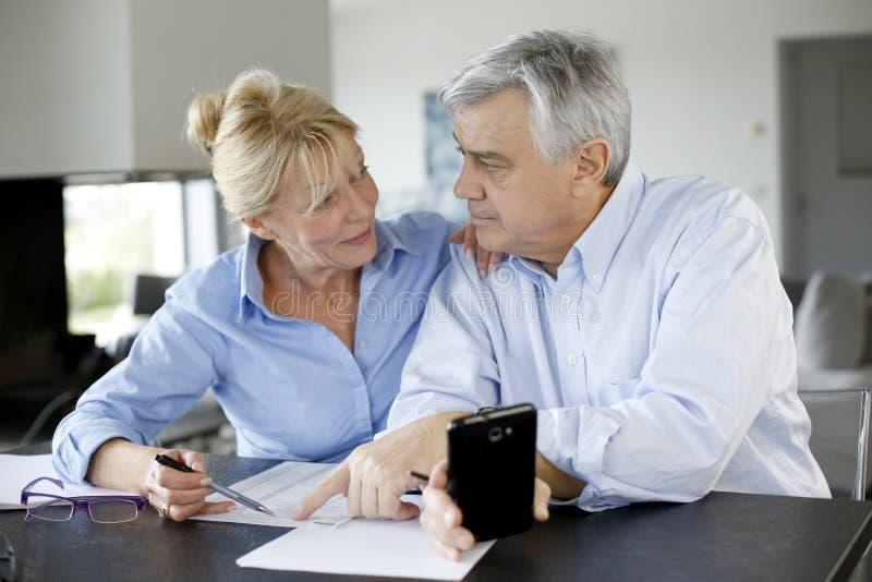 Senior couple calculating budget. Senior couple calculting bills amount using smartphone stock photos