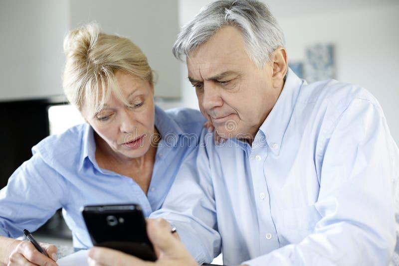 Senior couple calculating budget. Senior couple calculting bills amount using smartphone royalty free stock images