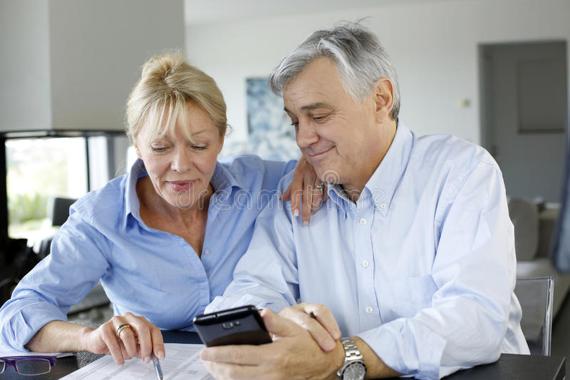 Senior couple calculating budget. Senior couple calculting bills amount using smartphone royalty free stock photography