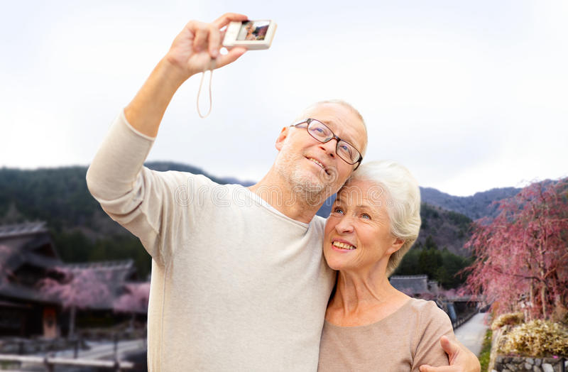 Senior couple with camera over asian village. Age, tourism, travel, technology and people concept - senior couple with camera taking selfie over asian village royalty free stock photos