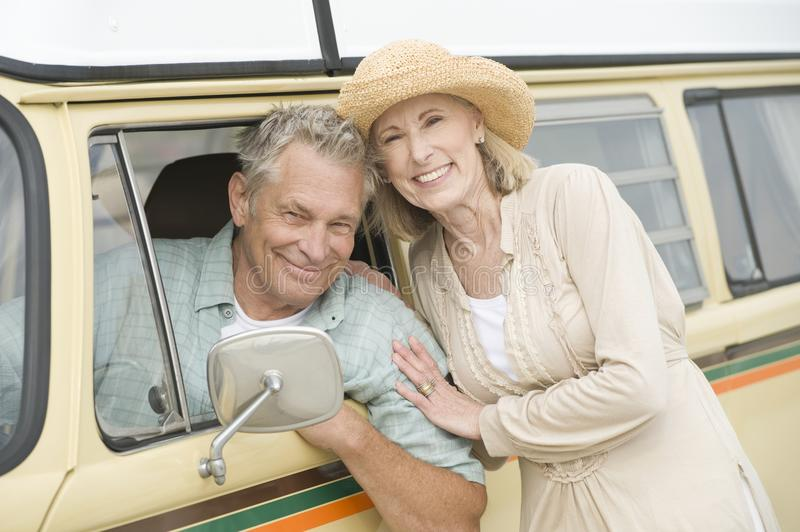 Senior Couple With Campervan. Portrait of happy senior couple with campervan stock images