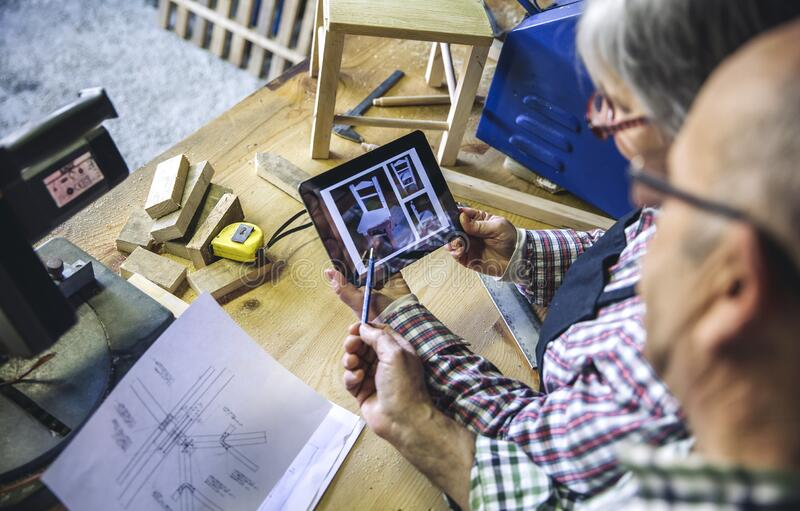 Senior couple in a carpentry looking tablet royalty free stock image