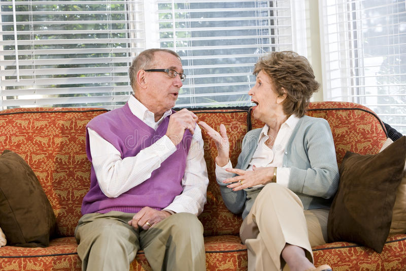 Senior couple chatting on living room couch. Senior couple talking together on living room couch stock photography