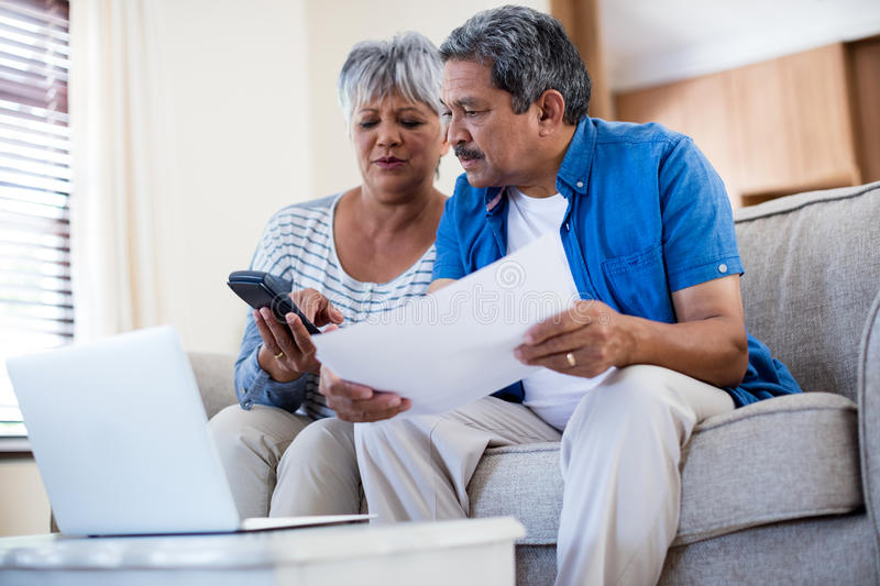 Senior couple checking bills in living room. At home stock photography