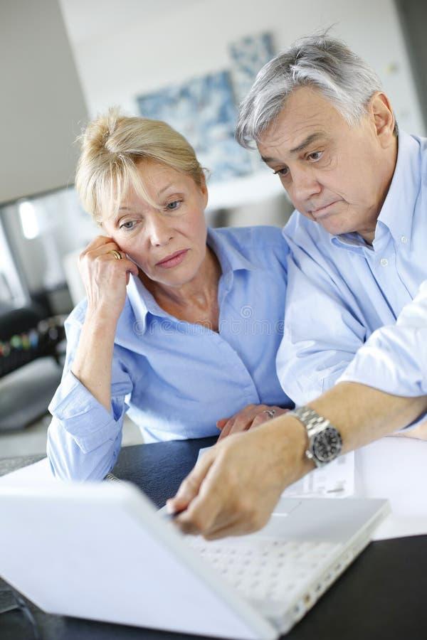 Senior couple checking their bank account on internet. Senior couple inquiring bank website for help royalty free stock photos
