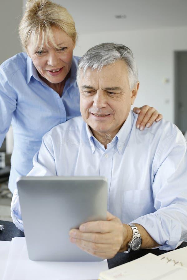 Senior couple checking their bank account. Senior couple looking at bank account on digital tablet stock photo