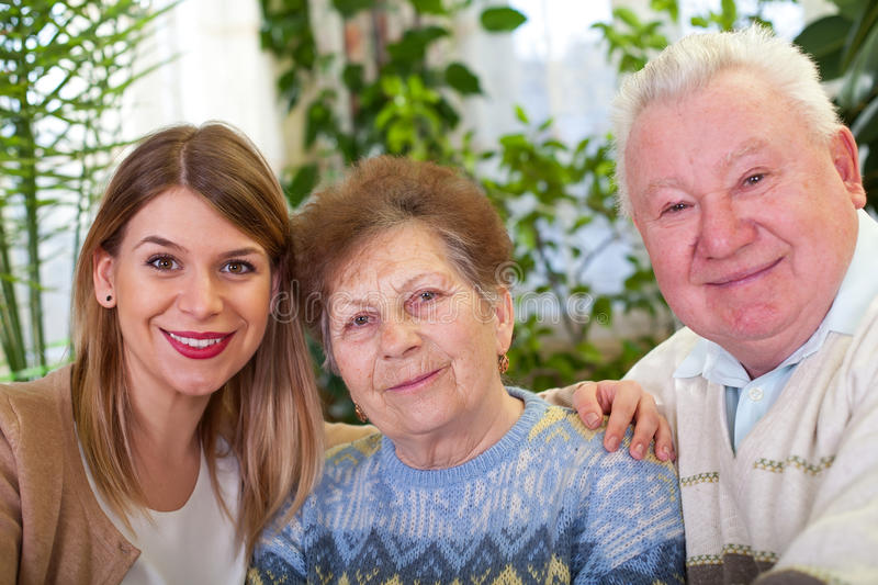 Senior couple with cheerful caregiver. Picture of a senior couple with their cheerful caregiver at home stock photos
