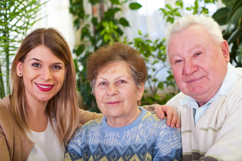 Senior couple with cheerful caregiver. Picture of a senior couple with their cheerful caregiver at home royalty free stock image