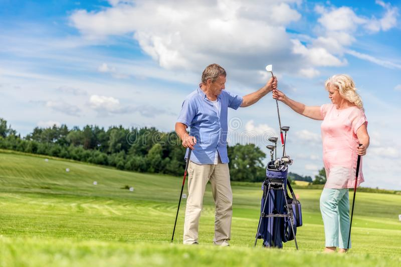 Senior couple choosing equipment for a golf game. Senior couple choosing equipment from a golf bag full of clubs. Active retirement and summer fun royalty free stock photo