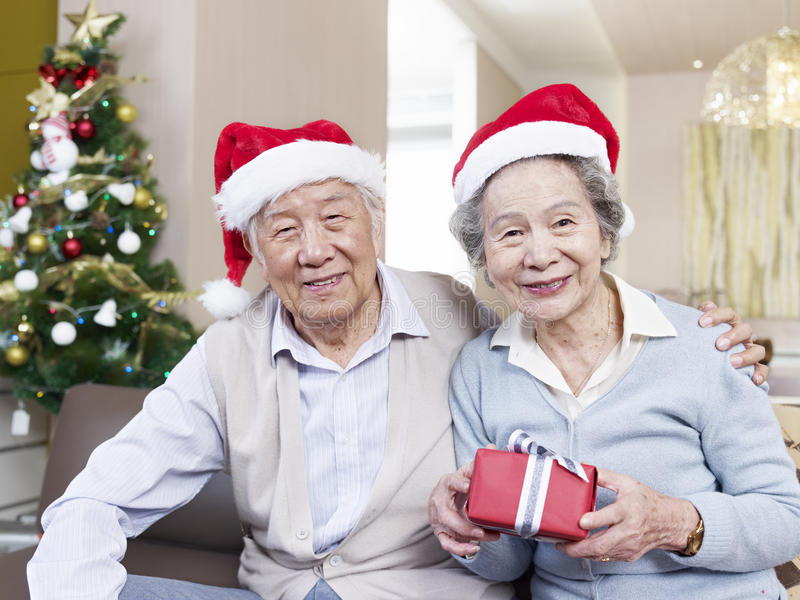 Senior couple with christmas hats. Portrait of an Asian senior couple with Christmas hats and gifts royalty free stock image