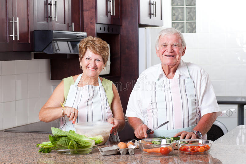 Senior couple cooking. Happy senior couple cooking in home kitchen royalty free stock images