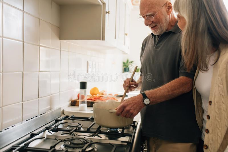 Senior couple cooking food together at home stock images