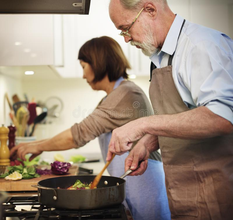 Senior couple cooking together in the kitchen stock photography