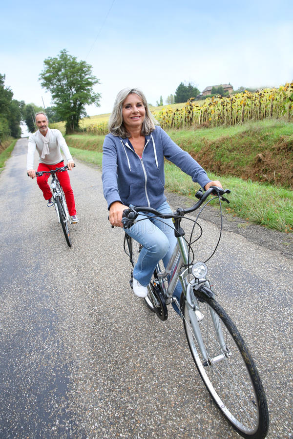 Senior couple crossing countryside with bicycle stock photography