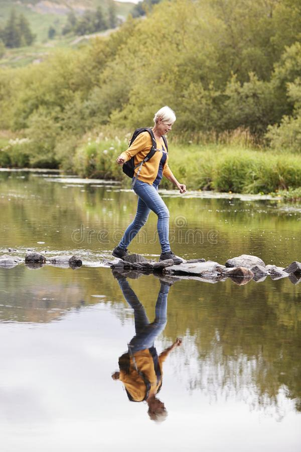 Senior Couple Crossing River Whilst Hiking In UK Lake District royalty free stock image