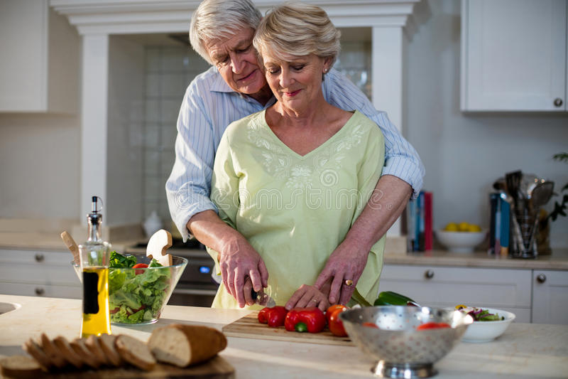 Senior couple cutting vegetables in kitchen royalty free stock image