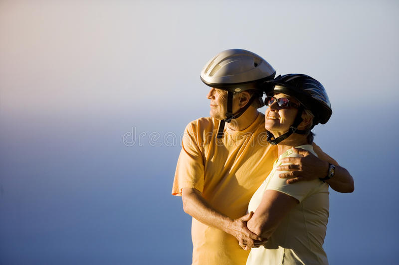 Senior couple, in cycling helmets, embracing on clifftop, looking at Atlantic Ocean horizon, side view stock photos