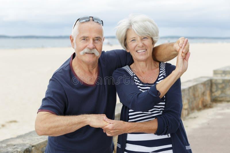Senior couple dancing at beach royalty free stock photo