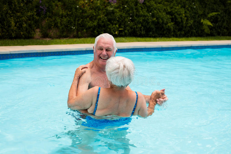 Senior couple dancing in the pool royalty free stock images