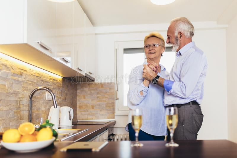 Senior couple dancing together at home stock image